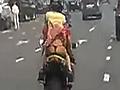 摩托车后座女子裙子被风吹起走光