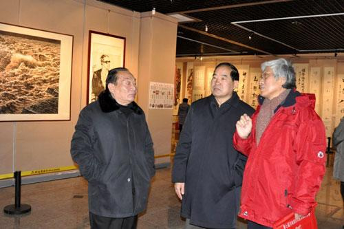 刘万林先生(右一)为原河南省人大常委会副主任李志斌(中)、原河南省军区司令员朱超少将(左)讲解作品