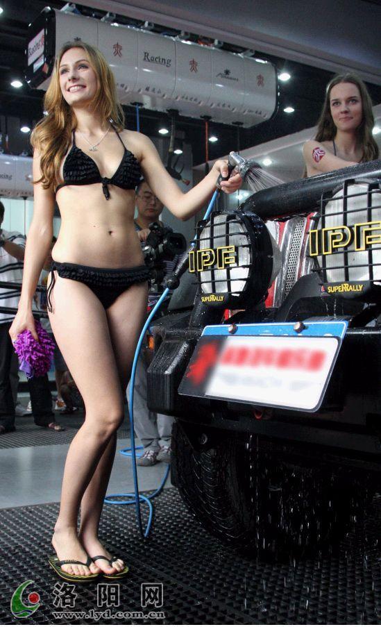 俄罗斯模特身着比基尼在一辆红色的豪华越野车前表演