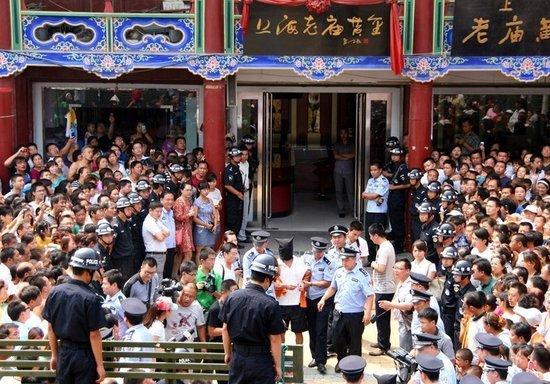 图为指认现场,闻讯赶到的群众将现场围得水泄不通,纷纷要目睹嫌疑人真面目。