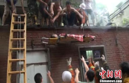 男孩躺在担架上被从房顶救下来 耿国锋 摄