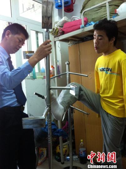无臂大学生吴建平与交警商量进一步修改不锈钢架子。 曹铮 摄