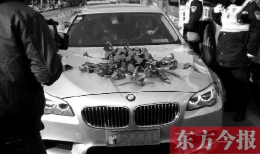 """1月1日上午,一辆故意粘贴""""百年好合""""的宝马婚车被郑州交巡警查扣"""