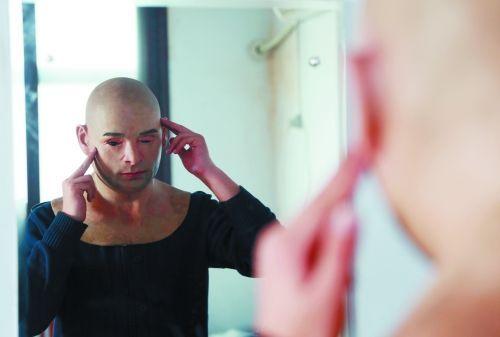 """记者亲自试戴""""人皮面具"""",正在镜子前调整眼睛、鼻子、嘴巴、耳朵的位置"""